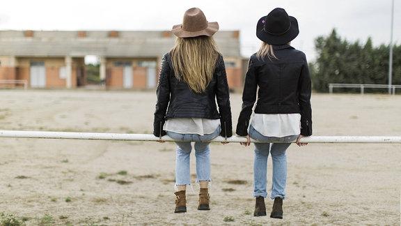 Zwei Freundinnen sitzen auf einem Zaun.