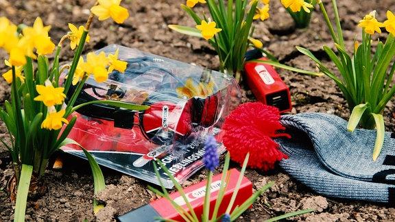 SPUTNIK Kopfhörer, SPUTNIK Powerbank und SPUTNIK Mütze zwischen Blumen liegend.