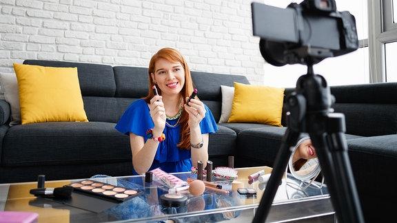 Junge Frau präsentiert Kosmetika vor der Kamera