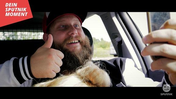 Ein SPUTNIK Hörer macht ein Selfie im Auto, während der Kopf einer Frau scheinbar über seinem Schoß ragt