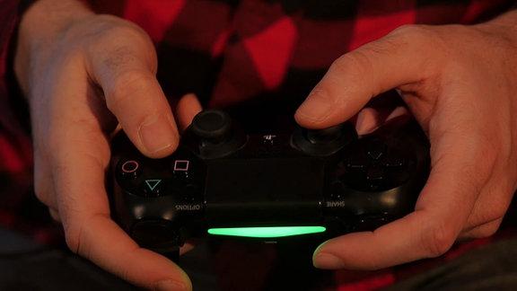 Playstation-Konsole in der Hand