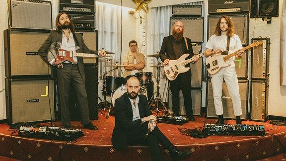 Die fünf Jungs von Idles - bärtig, langhaarig oder glatzköpfig - in schicken Anzügen vor einer Wand aus Lautsprechern. Der Schlagzeuger sieht als einziger aus wie ein Normie.