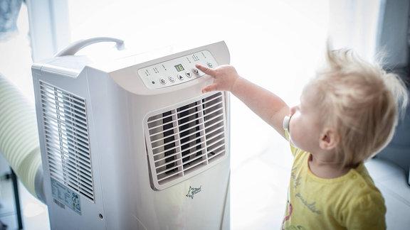 Kleinkind bedient eine Klimaanlage.