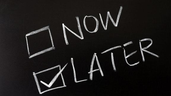 """Auf einer Tafel stehen die Wörter """"Now"""" und """"Later"""". Later wurde abgehakt."""