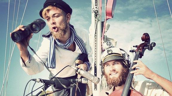Bandmitglieder Hannes und Benjamin auf einem Schiff mit Instrumenten und von Mikrofonen umringt.