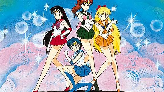 Die vier Heldinnen posieren vor einem bunten Hintergrund.