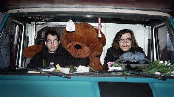 Myths Of A Thistle im Auto, ein großer Teddy fährt mit, ist aber nicht angeschnallt.