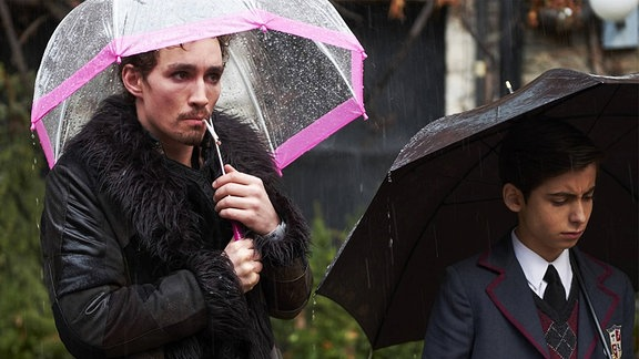 Robert Sheehan und Aidan Gallagher als ungleiche Brüder. Beide stehen nebeneinander im Regen mit Schirmen.