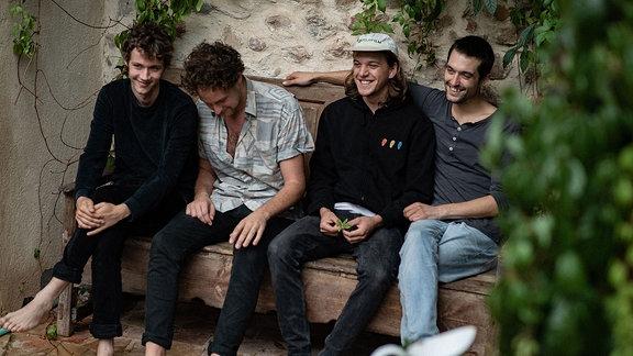 Die Musiker von Annemaykantereit sitzen nebeneinander auf einer Bank