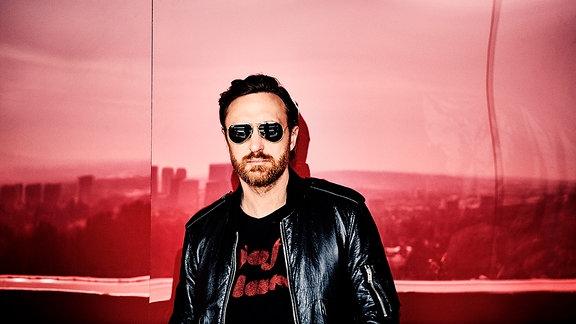 David Guetta mit schwarzer Lederjacke und Sonnenbrill vor einer weinroten Wand