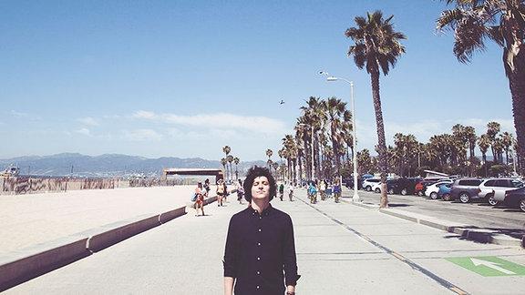 Der Künstler steht in schwarzem Hemd, mit geschlossenen Augen und dunklen Locken auf einer mit Palmen gesäumten Strandpromenade. Das Bild ist sonnenlichtdurchflutet, links ist Strand, rechts parken Autos. Im Hintergrund, ist eine Menschengruppe zu sehen. Der Himmel ist blau.