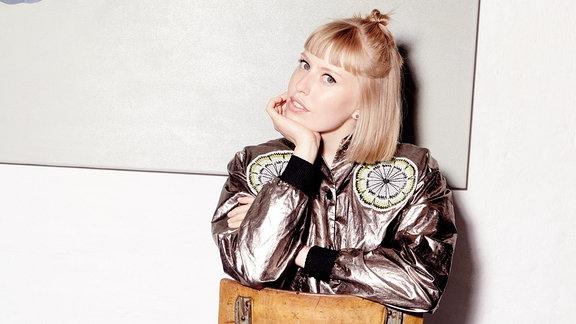 Sängerin Lea sitzend auf einem Stuhl.