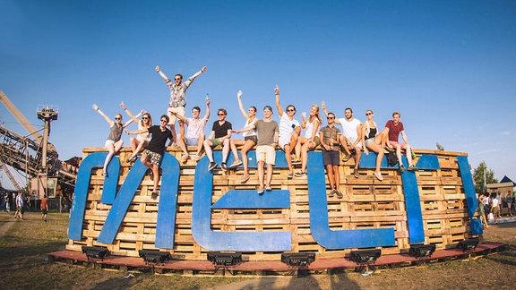Viele junge Festivalbesucher sitzen auf einm MELT-SCHRIFTZUF der aus Holzpalette gebaut ist. Der Himmel ist strahlend blau. Viele der Leute tragen Sonnenbrillen und recken die Arme nach oben.