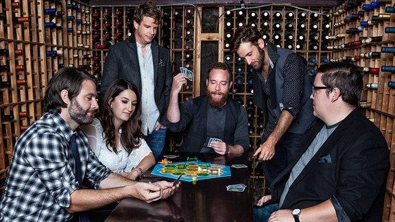Alle sechs Bandmitglieder sind um einen Tisch gruppiert. Zwei stehen, vier sitzen. Auf dem Tisch vor ihnen ist ein Gesellschaftsspiel aufgebaut, welches sie spielen. Die ganze Szene spielt sich in einem Weinkeller ab. Die Wände zieren unzählige Weinflaschen.