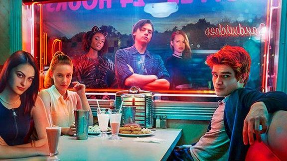 Jugendliche sitzen in einem neon-erstrahltem American Diner.