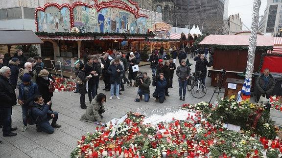 Menschen gedenken den Opfern des Anschlags in Berlin und legen Blumen nieder.