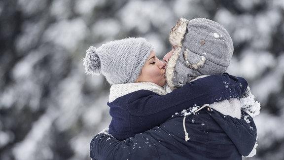 Sich küssendes Pärchen in einer Schneelandschaft.