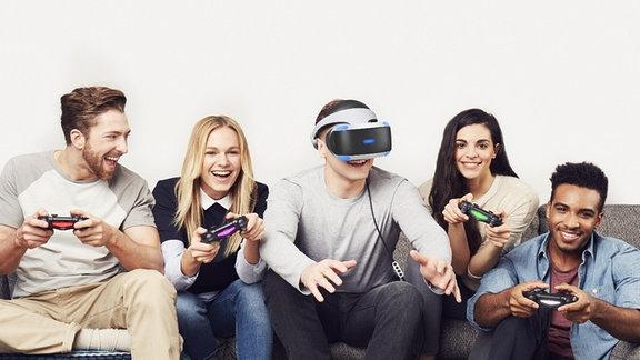 Gruppe von jungen Menschen, die mit der Playstation VR zocken.