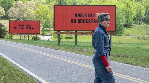 """Francis McDormand als Mildred Hayes in """"Three Billboards Ourside Ebbing, Missouri"""", läuft im blauen Overall über die Straße, im Hintergrund stehen zwei große Billboards"""