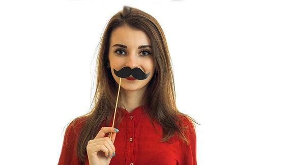 Frau hält sich einen Papierschnurbart unter die Nase