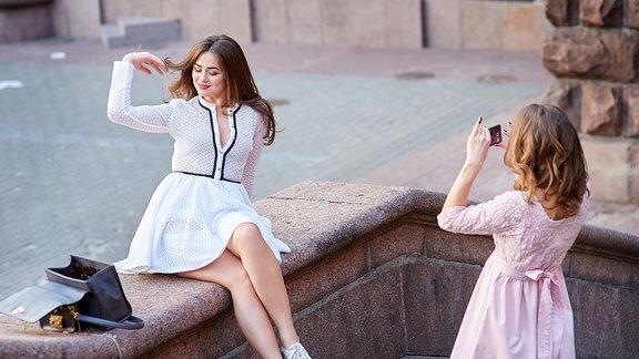 Junge Frau in Pose, lässt sich von einer Freundin mit Smartphone fotografieren