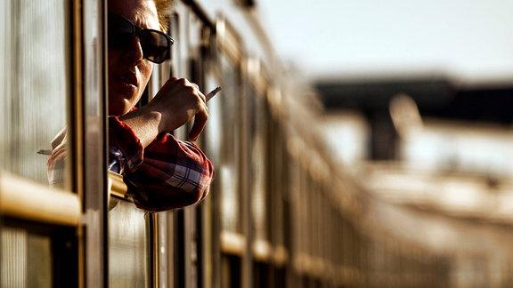 Typ schaut, eine Zigarette rauchend, aus einem geöffneten Zugfenster.