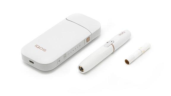 IQOS (I quit ordinary smoking) System, bestehend aus Charger (linlks), Erhitzungsgerät (mitte) und Tabakstick