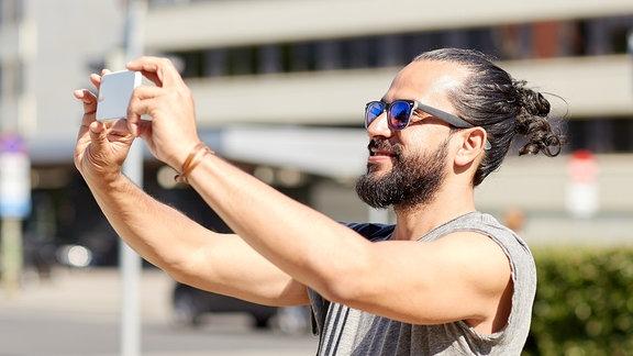 Typ mit Sonnenbrille, Zopf und Bart macht Selfieportrait von sich