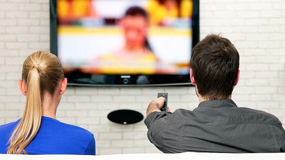 Pärchen sitzt vor dem Fernseher, Blick aus dem Hintergrund