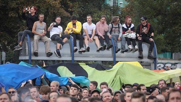 Zuschauer haben sich auf dem Dach eines Haltestellenhäuschens plaziert um sich das Konzert anzuhören, Chemnitz #wirsindmehr