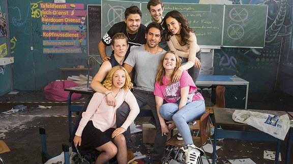 Herr Müller umringt von seiner Chaostruppe inmitten eines verwüsteten Klassenzimmers