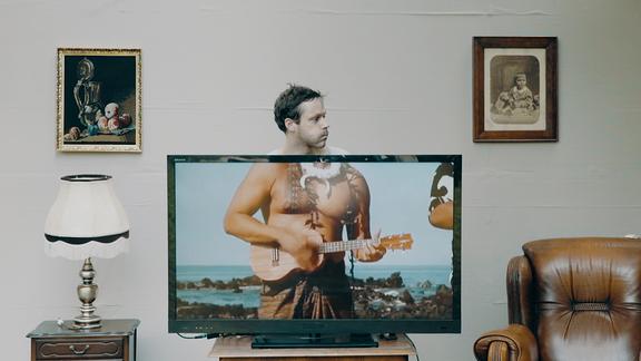 """Szene aus dem Musikvideo zu """"Palmen am Balkon"""". Sänger Thomas Petritsch steht hinter einem Fernseher und wird durch wechselnde Videos """"unterkörpert""""."""