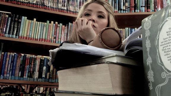 Eine blonde junge Frau sitz über eine, Bücherstapel und schaut desillusioniert ins Nichts. Sie wirkt sehr erschöpft.