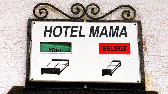"""Ein Schild mit der Aufschrift """"Hotel Mama"""". Das Einzelbett ist mit """"belegt"""" gekennzeichnet, das Doppelbett ist mit """"frei"""" gekennzeichnet."""