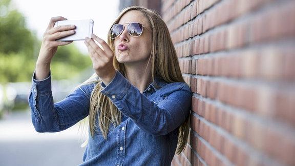 Junge Frau macht ein Selfie von sich.