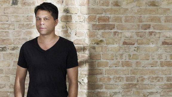 Markus Kavka in einem schwarzen T-Shirt vor einer Steinwand