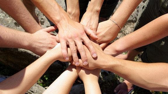 Ein Team legt die Hände übereinander.